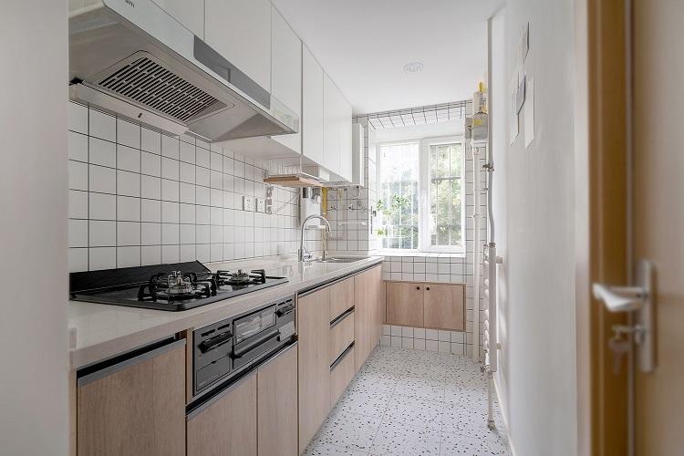 厨房空间橱柜材质是爱格板,地柜的木色小白砖加白色顶柜使空间干净美观。烟机灶台是日本的一款比较适合不做爆炒的家