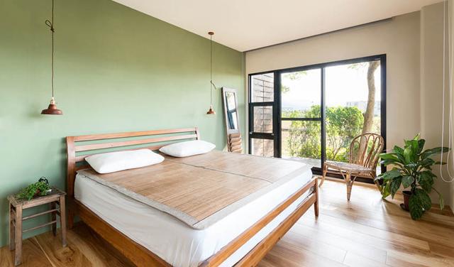 卧室维持简单自然风格,一抹绿色背景墙设计,突显视觉焦点又与户外绿意相呼应。落地窗为室内提供了良好采光与视线,空间明亮又简洁。