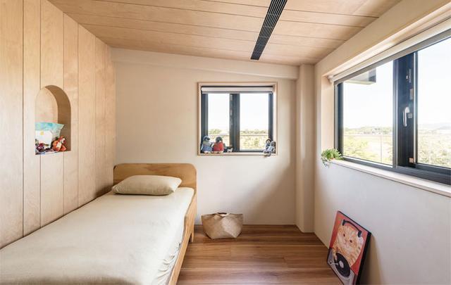 儿童房同样的维持简洁格调,满足基本需求及机能为主。木作由地面一直延伸到天花板,拉长视觉空间,衣柜和家具同样保持木色,维持格调的统一性。